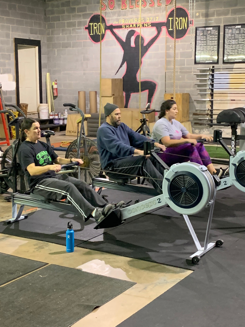 Misfit athletes Amanda, Scott, and Alex getting comfortable on the rower for a long, fun WOD!