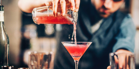 barman-preparing-and-pouring-red-cocktai