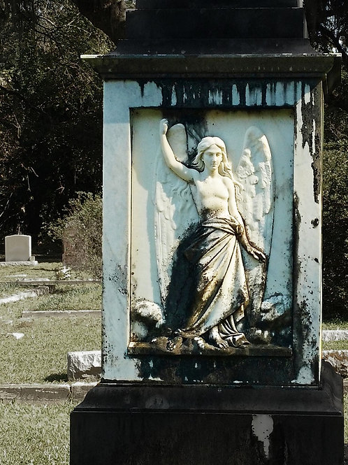 Carved Stone Angel guards obelisk in New Orleans Cemetery