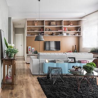 sala de televisão com estante e painel em folha de madeira