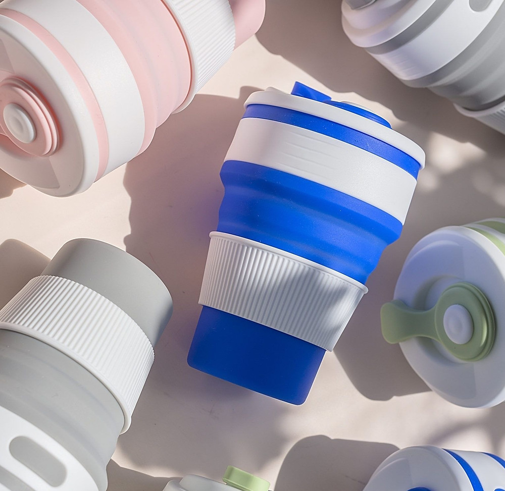 Image shows plastic cups on a light pink background with professional shadows setup.