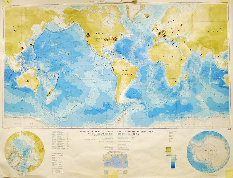 Bathymetric Chart of the Oceans with color-coded pins marking locations.  Yellow = birthplaces & family heritage sites, Red = education sites, Green = lab graduates, Blue = places members want to work or visit