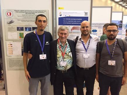 Serhat Sevgen, Dr. George Luther, Dr. Mustafa Yücel, and İsmail Akçay in front of poster presentation by Yücel and Sevgen during Goldschmidt 2019, Barcelona, Spain