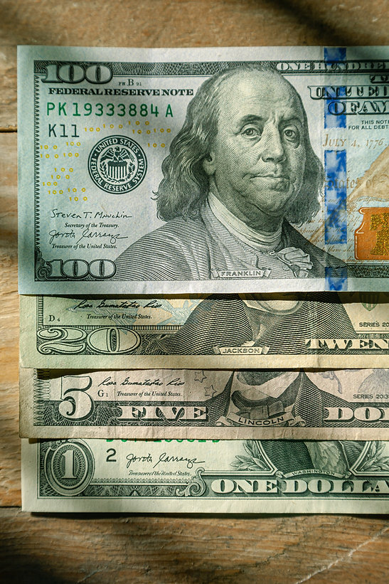 US%20Currency%20%24100%2C%20%2420%2C%20%245%2C%20%241%20denominations%20flat%20lay%20on%20wood%20bac