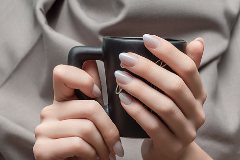 Female hands with white nail design. White nail polish manicure. Woman hold black coffee c