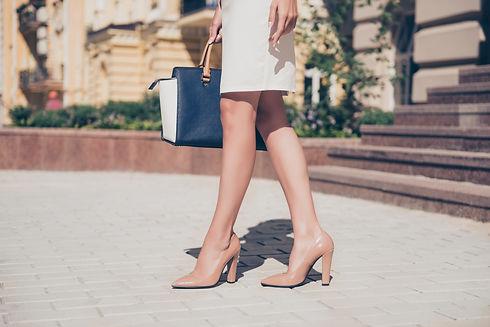 Close up of slim legs of woman wearing high heel shoes..jpg