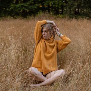 Zittend in trui in veldje
