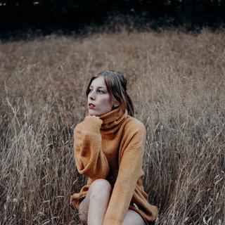 Zittend in een veldje met gele trui