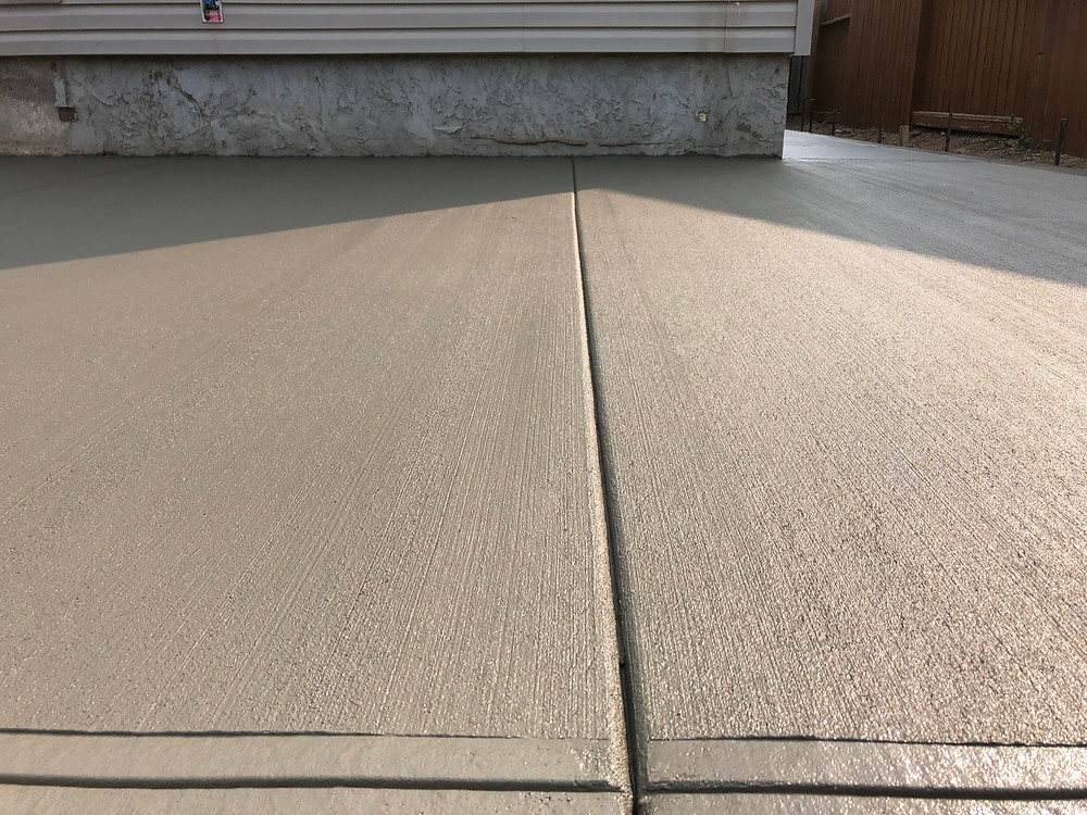Concrete patio in Regina installed by the concrete contractor Hepting concrete. This concrete pad has a broom finish and manual cut control joints to finish off this concrete pad.