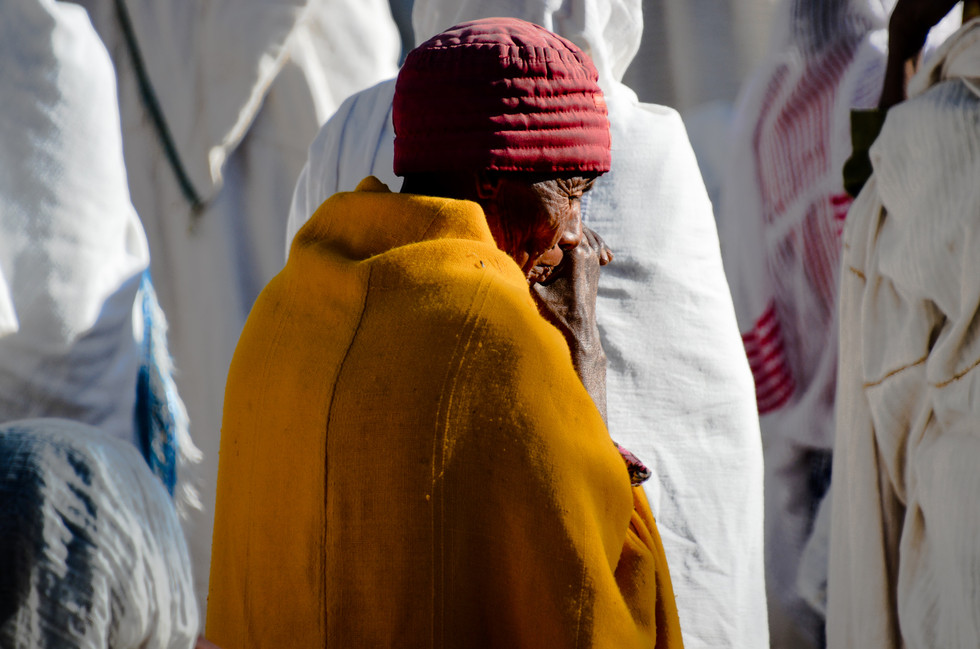 Worshipper in yellow at rock hewn church Sunday mass in Lalibela, Ethiopia