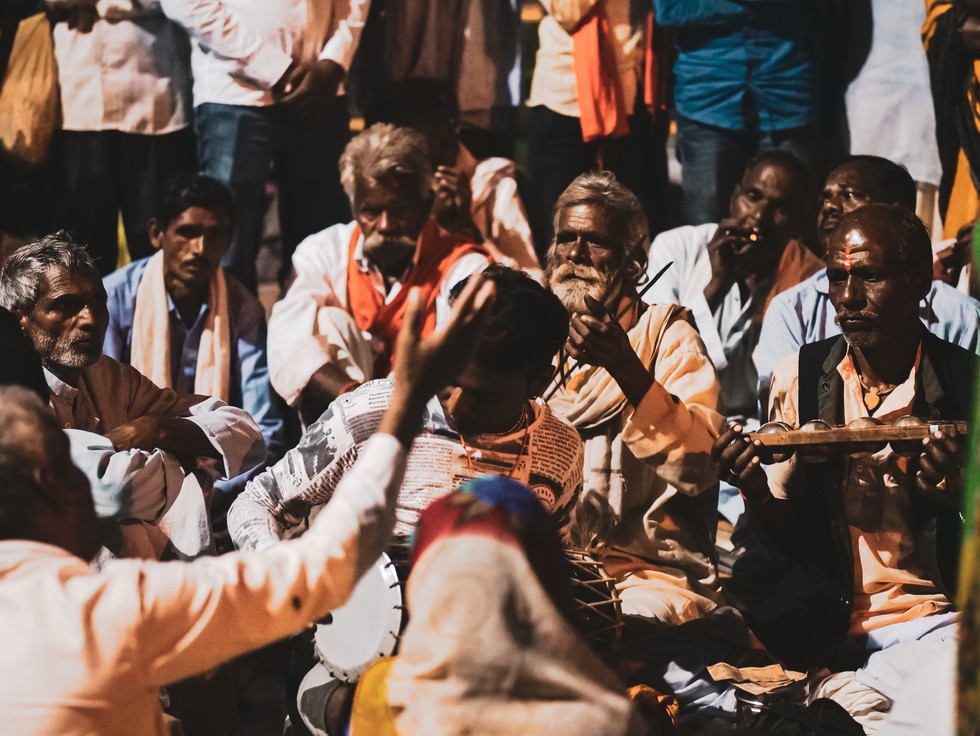 Circle of musicians drumming and singing to Ram Raja in Orchha, India