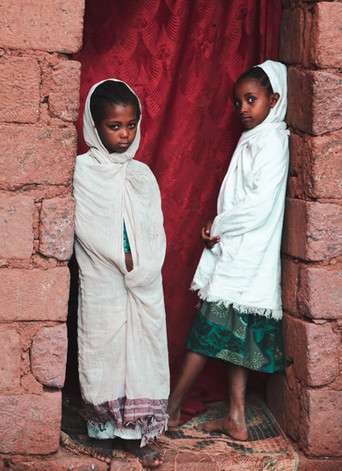 Two girls in doorway to rock hewn church in Lalibela, Ethiopia