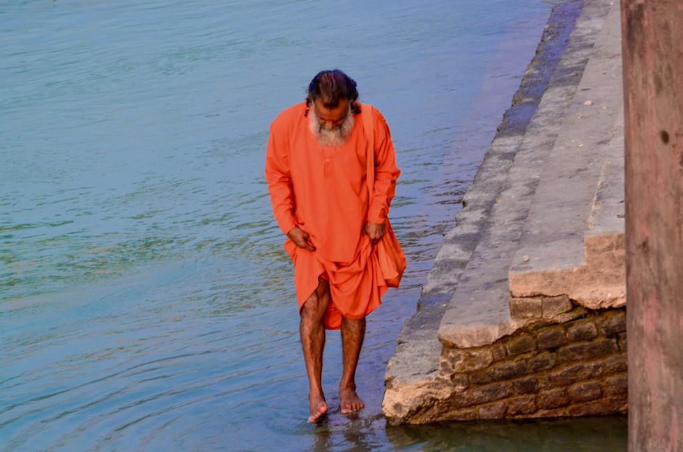 Saddhu in orange robes walking along Ganges River, Rishikesh, India