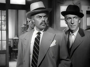 Marius Goring as Commandant Razinski and Wilfrid Hyde-White as Mr Luke in Highly Dangerous 1950