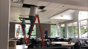 Two men on ladders replacing old light fixtures with new LED panels at the Skeena Valleyu Golf Course