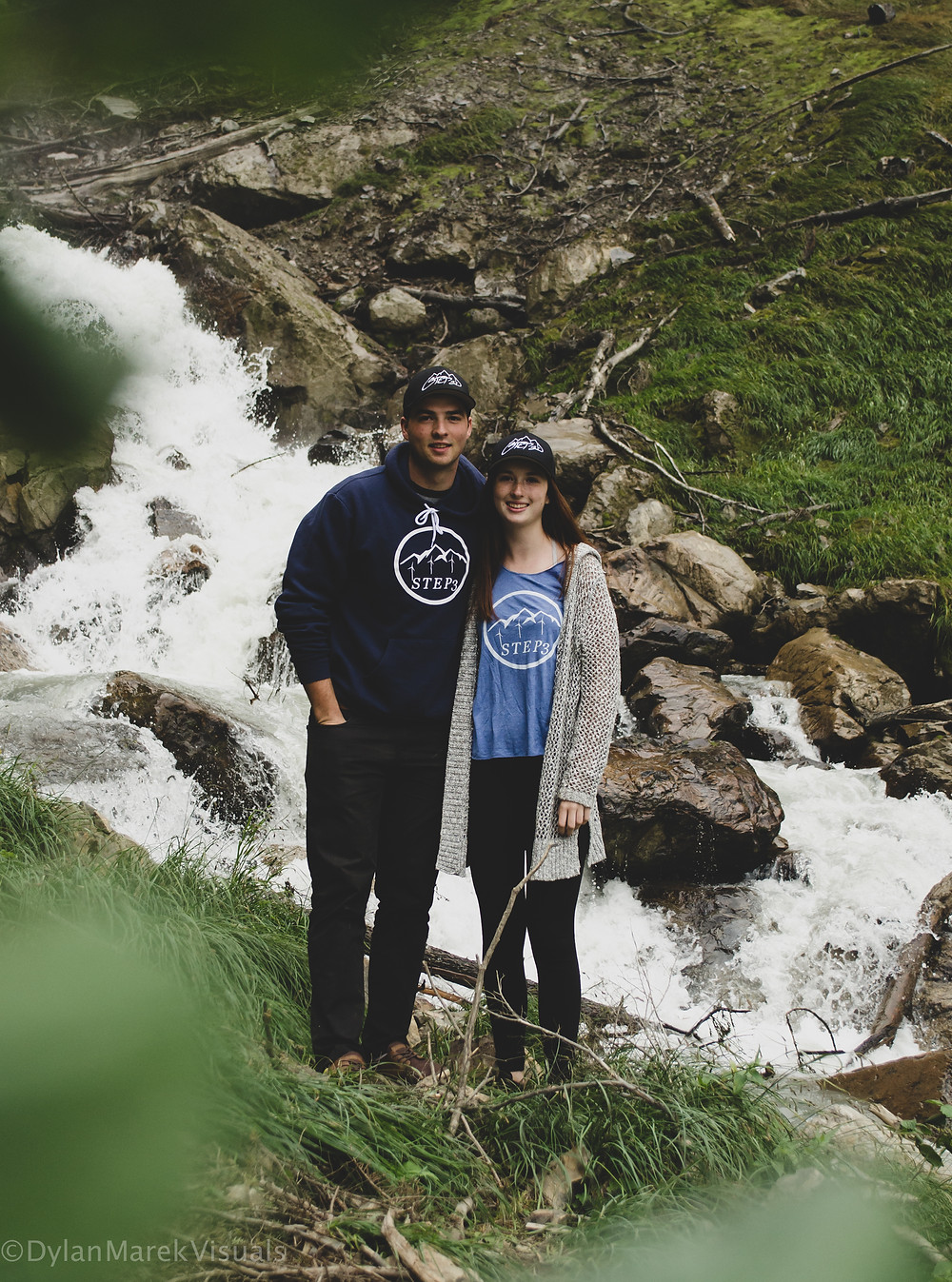 brother and sister standing in front of a river