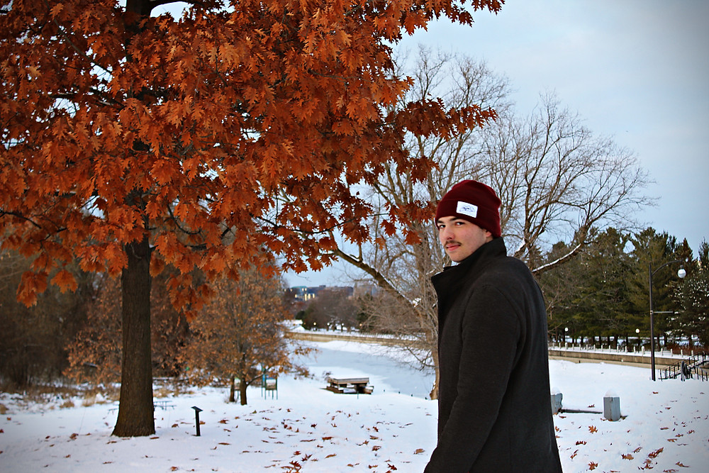 Man with moustache in step3 toque looking back at the camera in front of leaves changing colour