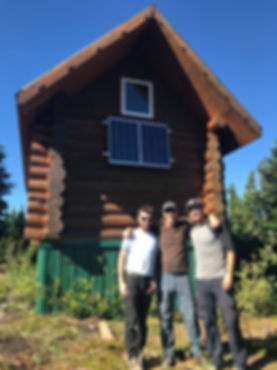 Larsen Ridge backcountry cabin powered by solar panels with three step3 representatives standin out front.
