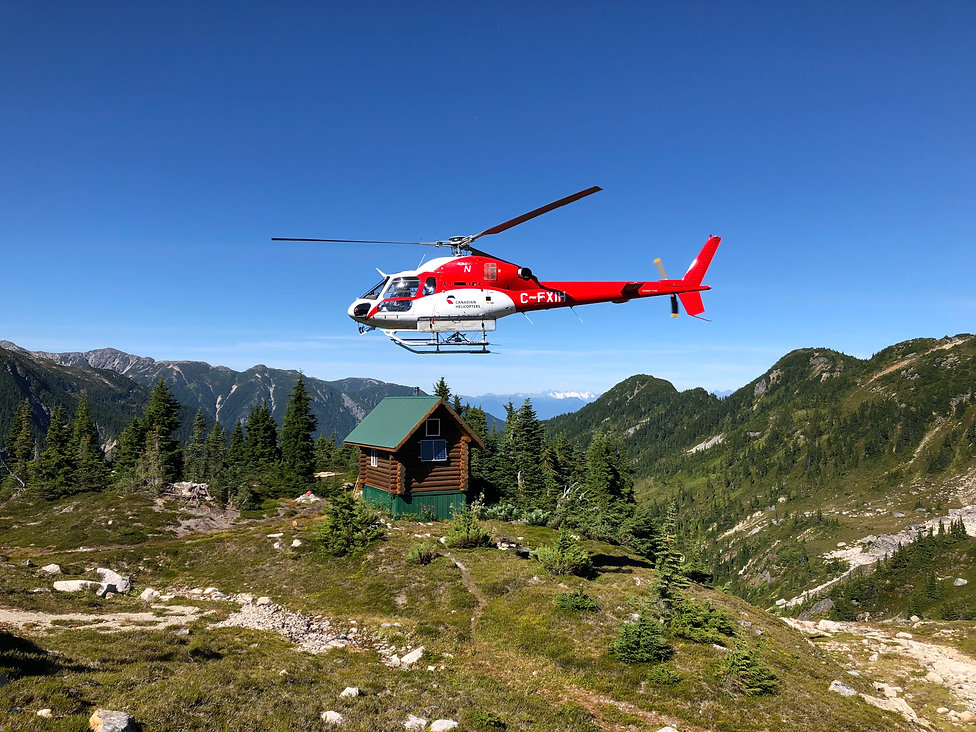 Canadian Helicopters in front of a newly solar powered Larsen Ridge Backcountry Cabin. Project copleted by Step3.