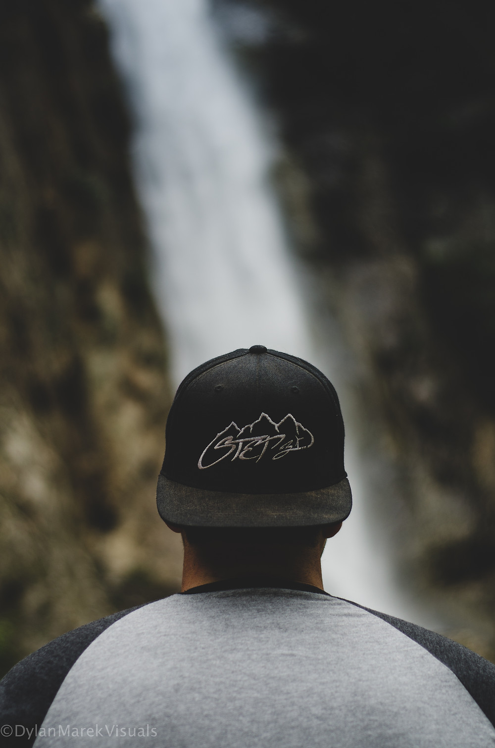 Man looking at a water fall in a backwards hat