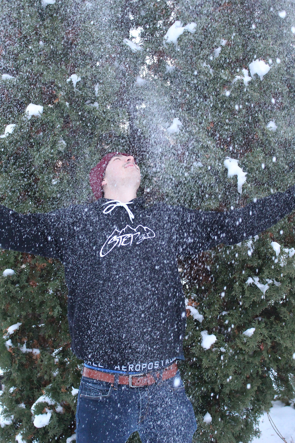 man in step3 hoodie throwing snow up in the air