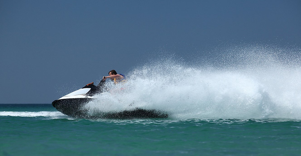 man on a jetski making a wave on the ocean
