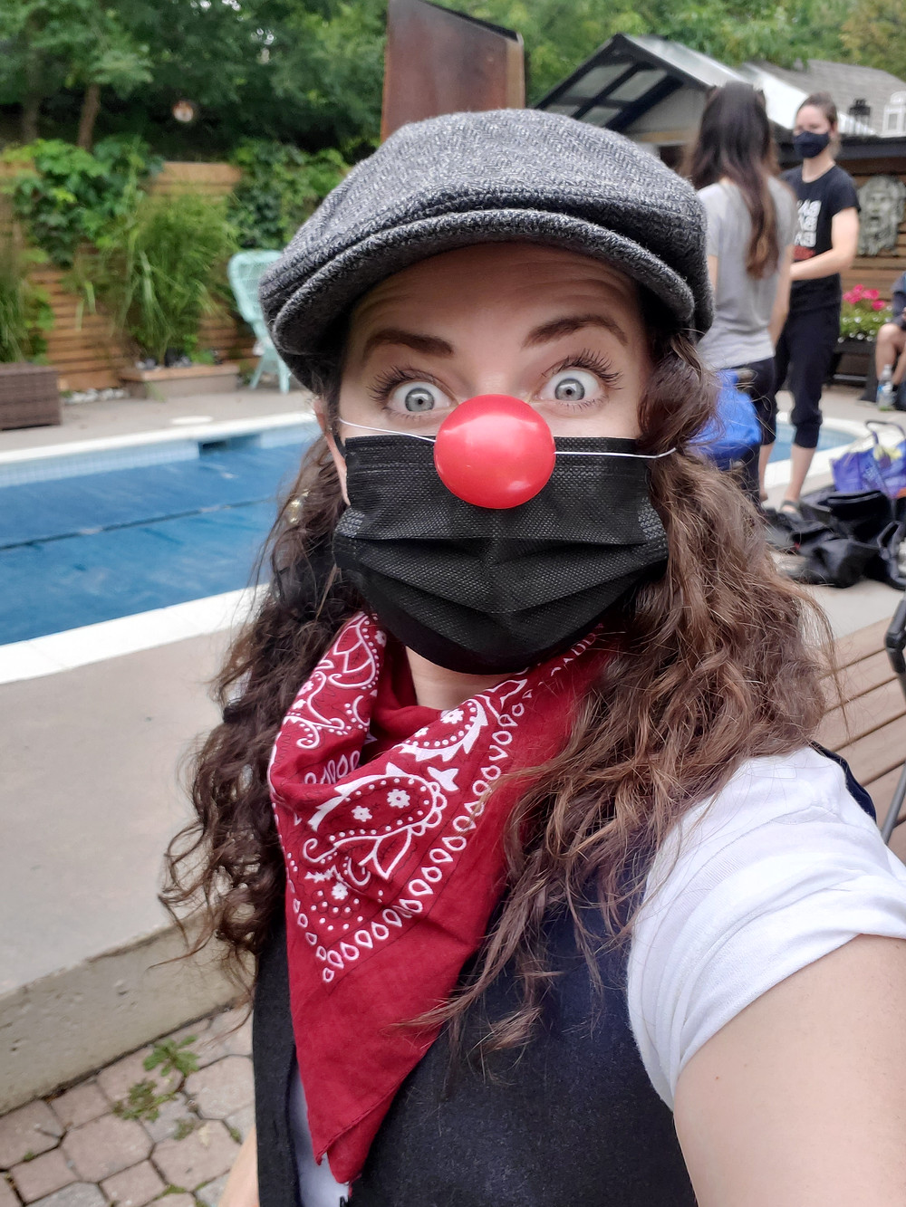 Person with red clown nose and grey hat taking a selfie