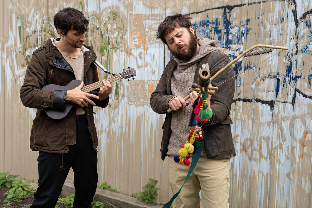 Two musicians jamming in front of beige wall