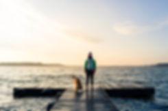 woman-with-dog-enjoy-sunrise-at-lake-bac