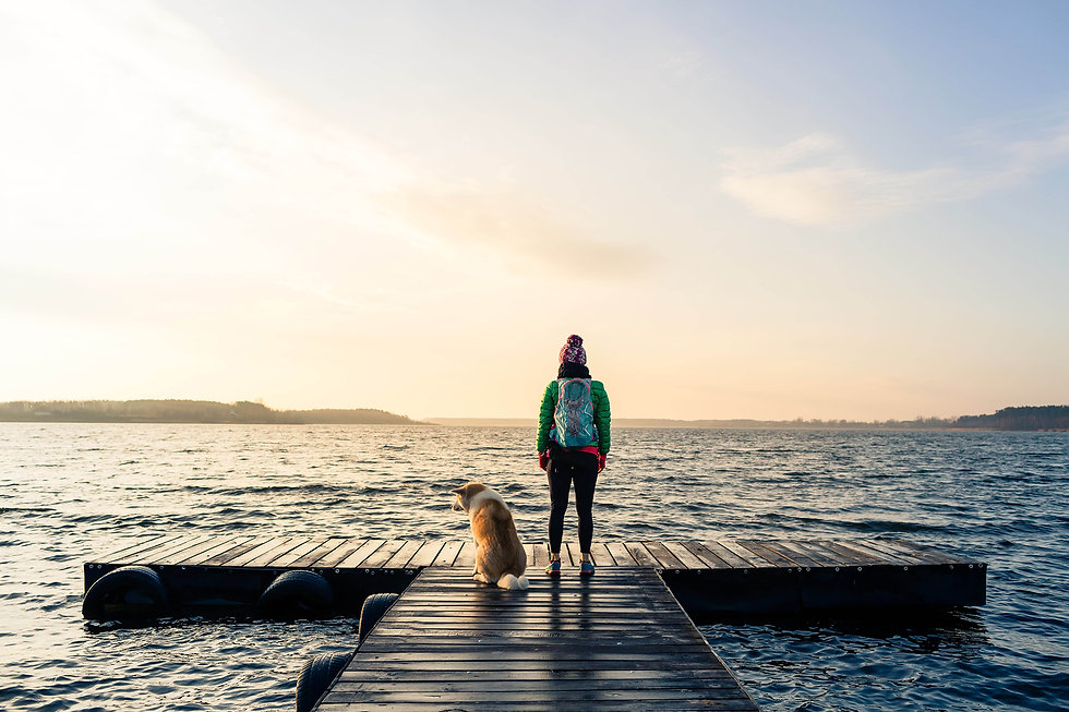 woman-with-dog-enjoy-sunrise-at-lake-bac