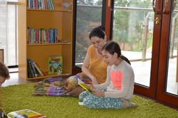 Student reading to teacher
