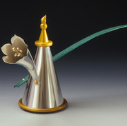 "Teapot 	2004 Gold, silver, anodized aluminum, and cork.  13.4"" (L) x 3.9"" (W) x 7.3"" (H)."