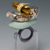 """""""Look beyond the adjectives""""  Ring        2013 Anodized aluminum, wild rice, Pyrex glass, brass, rock, cork, acrylic paint, Plexiglas, and laser printer ink.  2.25""""(L) x 1.75"""" (W) x 2.75"""" (H) Glass bottle credit: Benjamin Revis"""