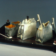 "Tea set      1989-90    Electroformed, fabricated and gold and silver- plated Silver, brass, copper, and ebony. Teapot:     9.8""(L) x 3.2""(W) x 6.7""(H)  Pitcher:   9.8""(L) x 3""(W) x 6.7(H)  Spoon:      7.9"" long Sugar bowl and creamer: Both 3.2 (L) x 2.6""(W) x 3.4(H)"