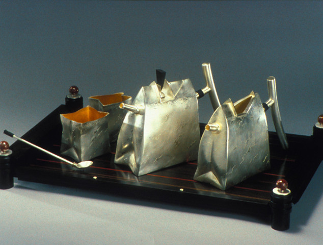 """Tea set      1989-90    Electroformed, fabricated and gold and silver- plated Silver, brass, copper, and ebony. Teapot:     9.8""""(L) x 3.2""""(W) x 6.7""""(H)  Pitcher:   9.8""""(L) x 3""""(W) x 6.7(H)  Spoon:      7.9"""" long Sugar bowl and creamer: Both 3.2 (L) x 2.6""""(W) x 3.4(H)"""
