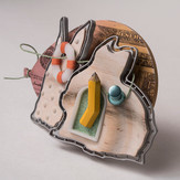 """""""Even rabbits crazy about money""""  (side view) Brooch   2017-8  Aluminum, maple, brass, enamel,  Delrin, Acrylic ink, laser printer ink, and thread.        4.5"""" (L) x 1.25"""" (W)  x 3"""" (H)"""