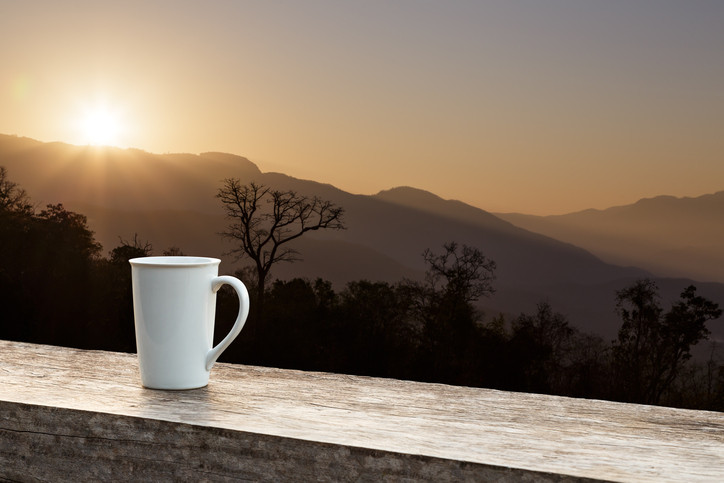 White mug on wood table with sunlight over mountain