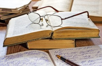 Opened notebook, pen, books and glasses