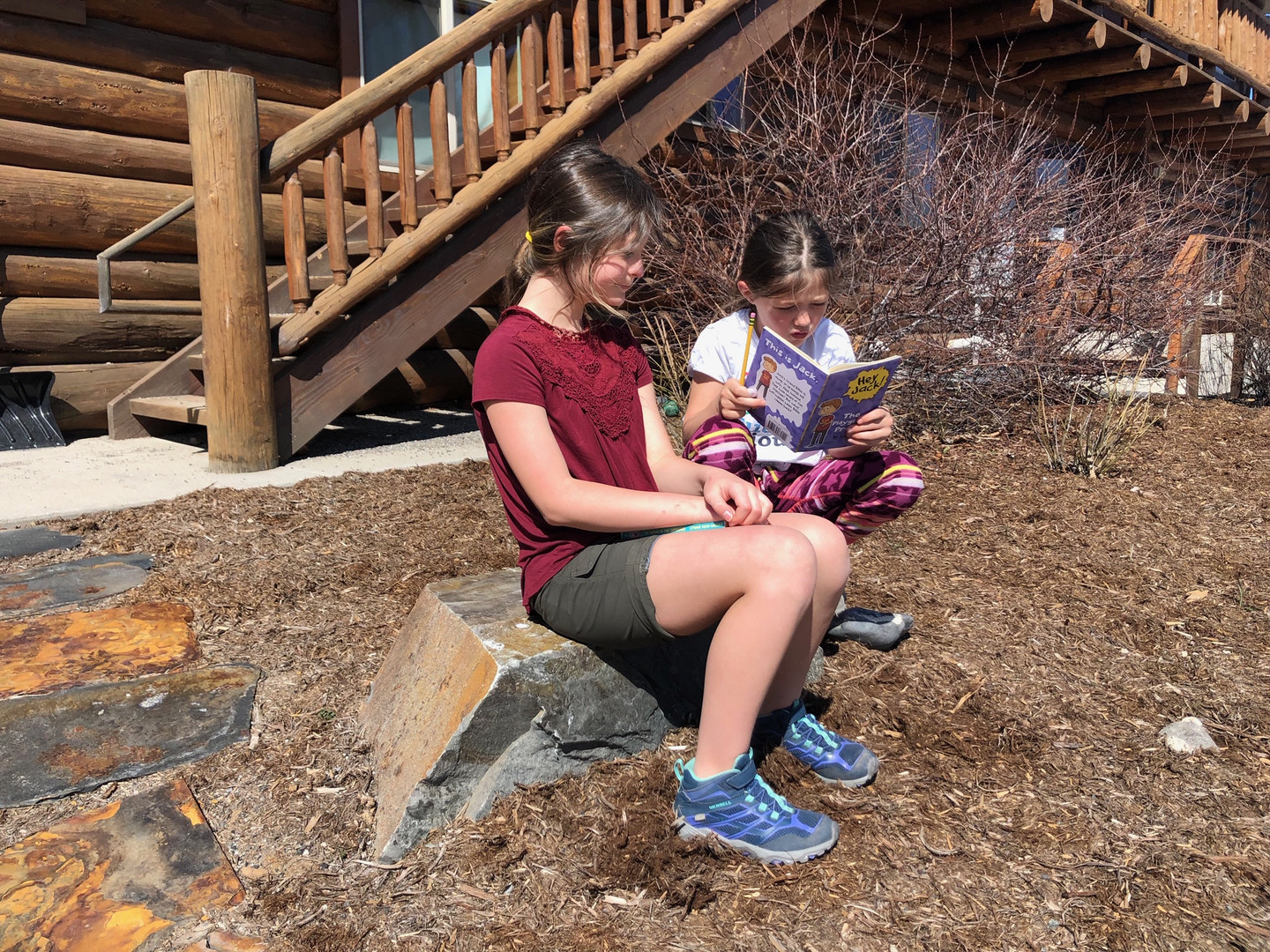 Girls reading outside of the Elementary building