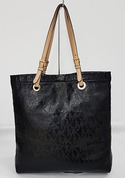 80fcd3370 Bolsa em material laminado cor preta, com estampa monograma, ferragens  douradas, forro interno com bolsos, fechamento por botão de pressão, alças  em couro ...