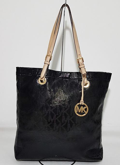 f48601061 Bolsa em material laminado cor preta, com estampa monograma, ferragens  douradas, forro interno com bolsos, fechamento por botão de pressão, alças  em couro ...