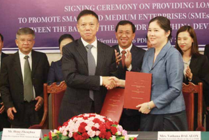 Deputy Governor of BOL, Mrs Vatthana Dalaloy, shakes hands with the President of China Development Bank's Yunnan Branch, Mr Hong Zhenghua, after signing an agreement on Wednesday as BOL Governor Mr Sonexay Sithphaxay looks on.