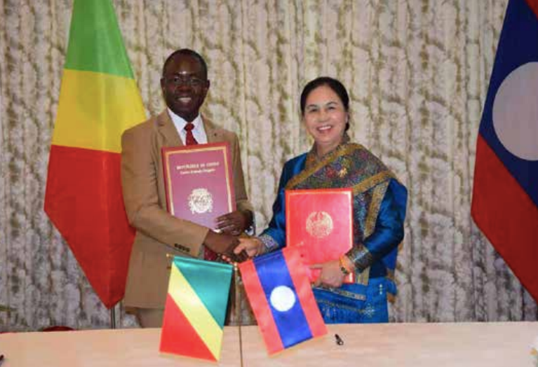 Ms Vandy Boudthasavong and Mr Daniel Owassa shake hands after signing the joint statement on diplomatic ties. –Photo Lao Embassy in Beijing