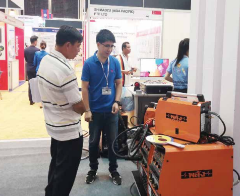 Customers view imported electronic products at an exhibition in Vientiane.