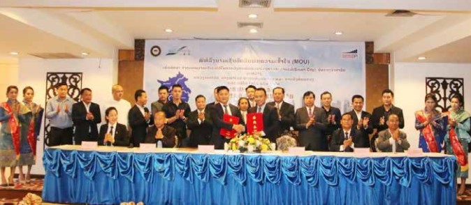 Dr Souksavanh Vilaivong (standing front right) shakes hands with Mr Chen Zunyan after signing the agreement.