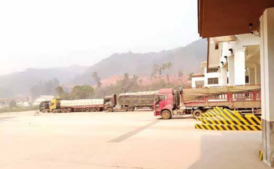 Trucks transport goods from China to Laos via Boten International checkpoint in Luang Namtha. International firms exporting goods to Laos will no longer need a domestic operations license