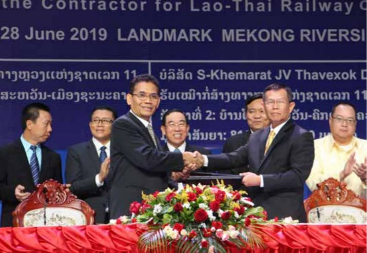 An official from the Department of Railways shakes hands with a Thai contractor at the MOU signing ceremony.