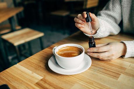 Adding CBD oil in a coffee cup.jpg
