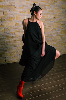NYC Female model posing in a black evening dress and red heels.