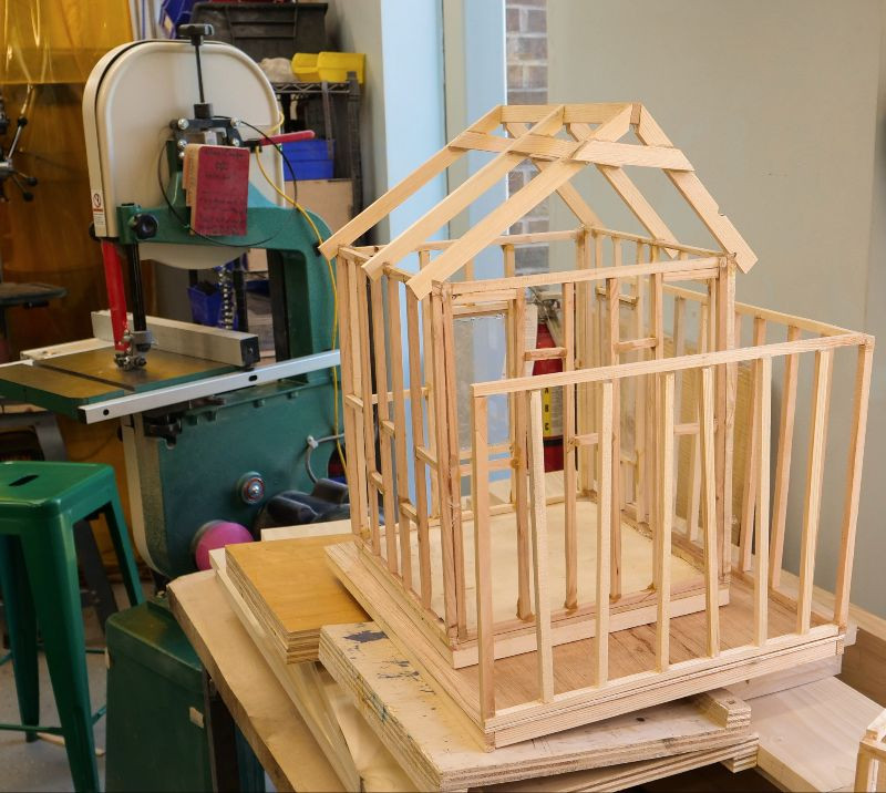 Framing for a model house made out of wood.